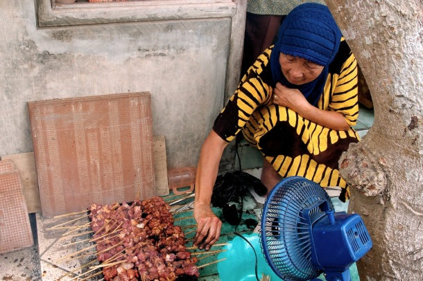 An elderly neighborhood woman cooking up sate for about 100 adults and children.