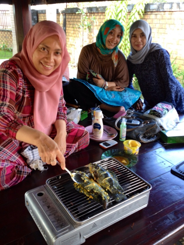 Bu Holifah trying to cure disappointments by inviting me to eat grilled fish with her family and friends.